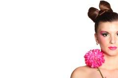 Junges Mädchen wie eine Puppe im rosafarbenen Kleid mit Blume Lizenzfreie Stockfotografie
