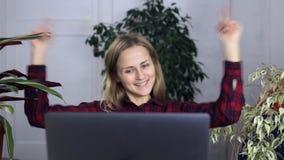 Junges Mädchen wird mit dem Ergebnis ihrer Arbeit gefallen, zeigt das Sitzen an einem Laptop mit ihren Händen ihre Freude und Erf stock footage