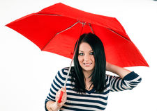 Junges Mädchen wird vor schlechtem Wetter mit einem roten Regenschirm geschützt Stockfotos