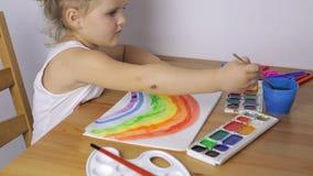 Junges Mädchen zeichnet einen bunten Regenbogen stock footage