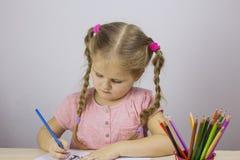 Junges Mädchen zeichnet mit farbigen Bleistiften getrennte alte Bücher Stockbild
