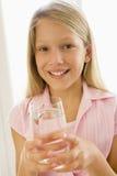Junges Mädchen zuhause das Trinkwasserlächeln Lizenzfreie Stockfotografie