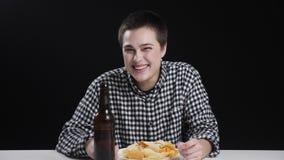 Junges männisches Mädchen beendet, Chips essend und Bier trinkend, lächelnd und lachen, Diätkonzeption, schwarzer Hintergrund stock video
