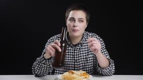 Junges männisches Mädchen trinkt das Bier und thhinking, Kartoffelchips auf Platte, Diätkonzeption, schwarzer Hintergrund 50fps stock footage