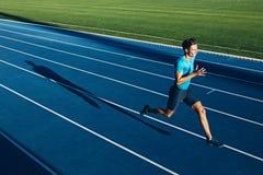 Junges männliches Athletentraining auf einer Rennstrecke Lizenzfreie Stockbilder