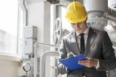 Junges männliches Aufsichtskraftschreiben auf Klemmbrett in der Industrie Stockbild