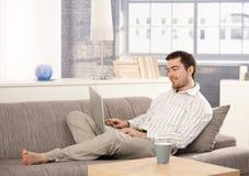 Junges männliches Durchstöbern Internet, das auf Sofa sitzt stockfoto