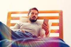 Junges männliches haltenes Mobiltelefon im Bett Lizenzfreie Stockfotografie