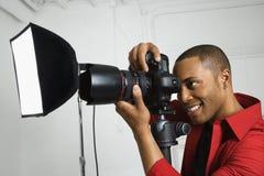 Junges männliches Schauen durch Kamera. Lizenzfreies Stockfoto