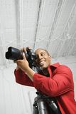Junges männliches Schauen durch Kamera. Lizenzfreies Stockbild
