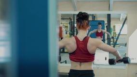 Junges M?dchen, athletisch, in der Turnhalle Sie hebt Dummk?pfe, ausbildet die Muskeln ihrer Schultern an stock video footage