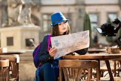 Junges M?dchen in einem blauen Hut, der auf der Sommerterrasse in der alten Stadt stillsteht und die Karte betrachtet Lemberg, Uk stockbild