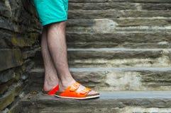 Junges man& x27; s-Beine mit den orange Neonpantoffeln, die auf Steintreppe stehen lizenzfreies stockbild