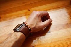 Junges man& x27; s-Hand mit einer Uhr- und Armbanddekoration Stockfotografie