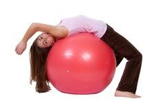 Junges Mädchen auf einer Übungs-Kugel Stockbild