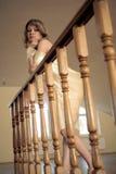 Junges Mädchen basiert auf geschnitztem hölzernem Geländer Stockfotos