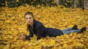 Junges Mädchen, das auf den Blättern im Park liegt Herbst Stockbild