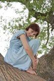 Junges Mädchen, das auf einem großen alten Baum sitzt Stockfoto