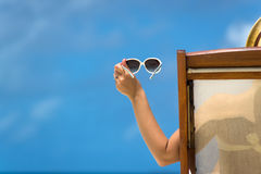 Junges Mädchen, das auf einem Strandruhesessel mit Gläsern in der Hand auf der Tropeninsel liegt Lizenzfreie Stockfotos