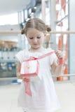 Junges Mädchen, das Band auf Geschenk auspackt Stockfoto