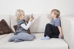 Junges Mädchen, das Bruder durch Handy auf Sofa fotografiert Stockfotos