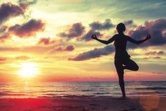 Junges Mädchen, das an der Yogahaltung auf dem Strand während eines erstaunlichen Sonnenuntergangs steht Stockfotografie