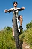 Junges Mädchen, das ein Fahrrad auf ein Feld reitet Lizenzfreie Stockfotos