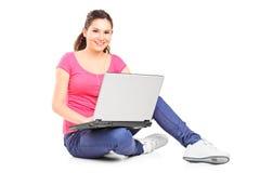 Junges Mädchen, das einen Laptop hält und Kamera betrachtet Stockfoto