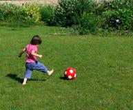 Junges Mädchen, das Fußball im Garten spielt Stockbilder