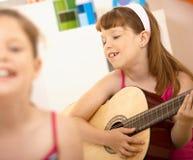 Junges Mädchen, das Gitarre spielend genießt Lizenzfreie Stockfotos
