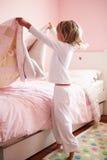 Junges Mädchen, das ihr Bett macht Stockfotos