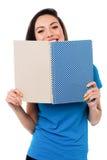Junges Mädchen, das ihr Gesicht mit Notizbuch versteckt Stockbild