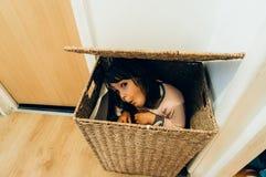 Junges Mädchen, das im Korb sich versteckt Stockfoto
