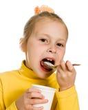 Junges Mädchen, das Joghurt isst Lizenzfreie Stockbilder