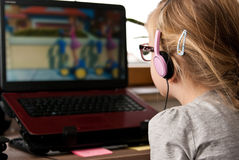 Junges Mädchen, das Laptopschirm betrachtet Stockfotos