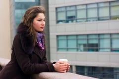 Junges Mädchen, das mit einem Tasse Kaffee denkt Stockfoto