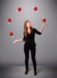 Junges Mädchen, das mit roten Bällen steht und jongliert Stockfotos