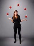 Junges Mädchen, das mit roten Kugeln steht und jongliert Stockfotos