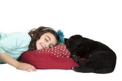 Junges Mädchen, das mit schwarzem Laborwelpen schläft Stockfoto