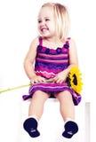 Junges Mädchen, das mit Sonnenblume lächelt Lizenzfreies Stockfoto