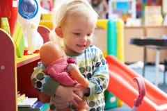 Junges Mädchen, das mit Spielwaren spielt Stockbilder