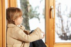 Junges Mädchen, das Snowy-Ansicht betrachtet Stockfoto