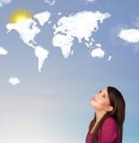 Junges Mädchen, das Weltwolken und -sonne auf blauem Himmel betrachtet Lizenzfreie Stockfotos