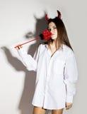 Junges Mädchen in einem Mann ` s weißen Hemd mit den roten Hörnern, die Dreizack und Aussehung wie hübscher Teufel halten Stockbilder