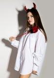 Junges Mädchen in einem Mann ` s weißen Hemd mit den roten Hörnern, die Dreizack und Aussehung wie hübscher Teufel halten Stockfoto