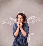Junges Mädchen mit dem Teufelhorn- und -flügelzeichnen Lizenzfreie Stockfotos
