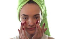 Junges Mädchen mit Tuch auf dem Haar verursacht eine Creme für das Gesicht und lächelt stock video footage
