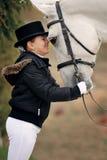 Junges Mädchen mit weißem Dressurreitenpferd Lizenzfreies Stockfoto