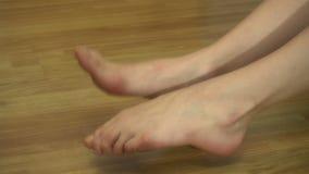 Junges Mädchen rüttelt ihre Füße und Finger auf beiden Beinen zu Hause stock video
