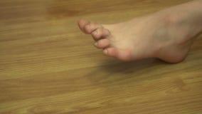 Junges Mädchen rüttelt ihre Füße und Finger auf einem Bein zu Hause stock video footage